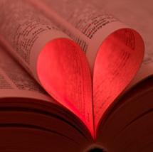 Shows an open book with a few pages tucked back into the spine to form the shape of a heart.