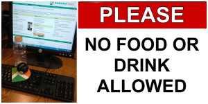 "A photograph focusing on a keyboard and computer monitor with a plum and water bottle. Text says, ""Please no food or drink allowed"""