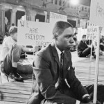 A young black man sitting down with a backdrop of protestors
