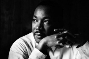Black and white photograph of Dr. Martin Luther King, Jr. with his hands clasped in front of him