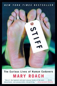 "Shows the feet of a corpse with a label, ""Stiff"""