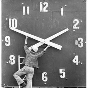 Image of a workman adjusting the hands on a large clock
