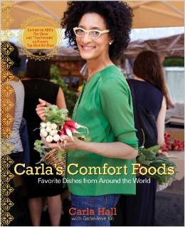 Carla Hall smiling and holding root vegetables.