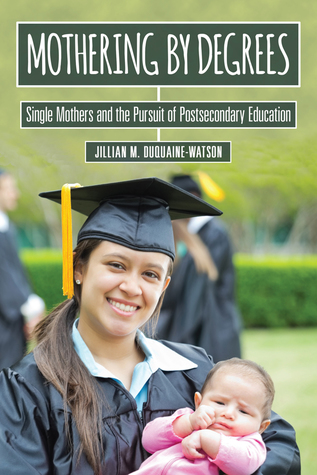A woman in a graduation cap and gown holding a baby.