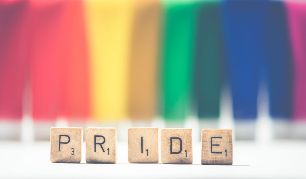 PRIDE Scrabble letters on a faded rainbow background